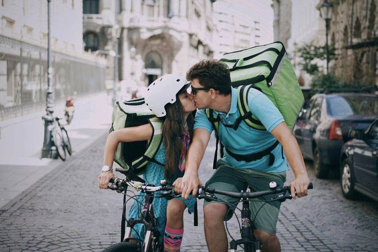 Couple kissing while riding bicycles on street in city