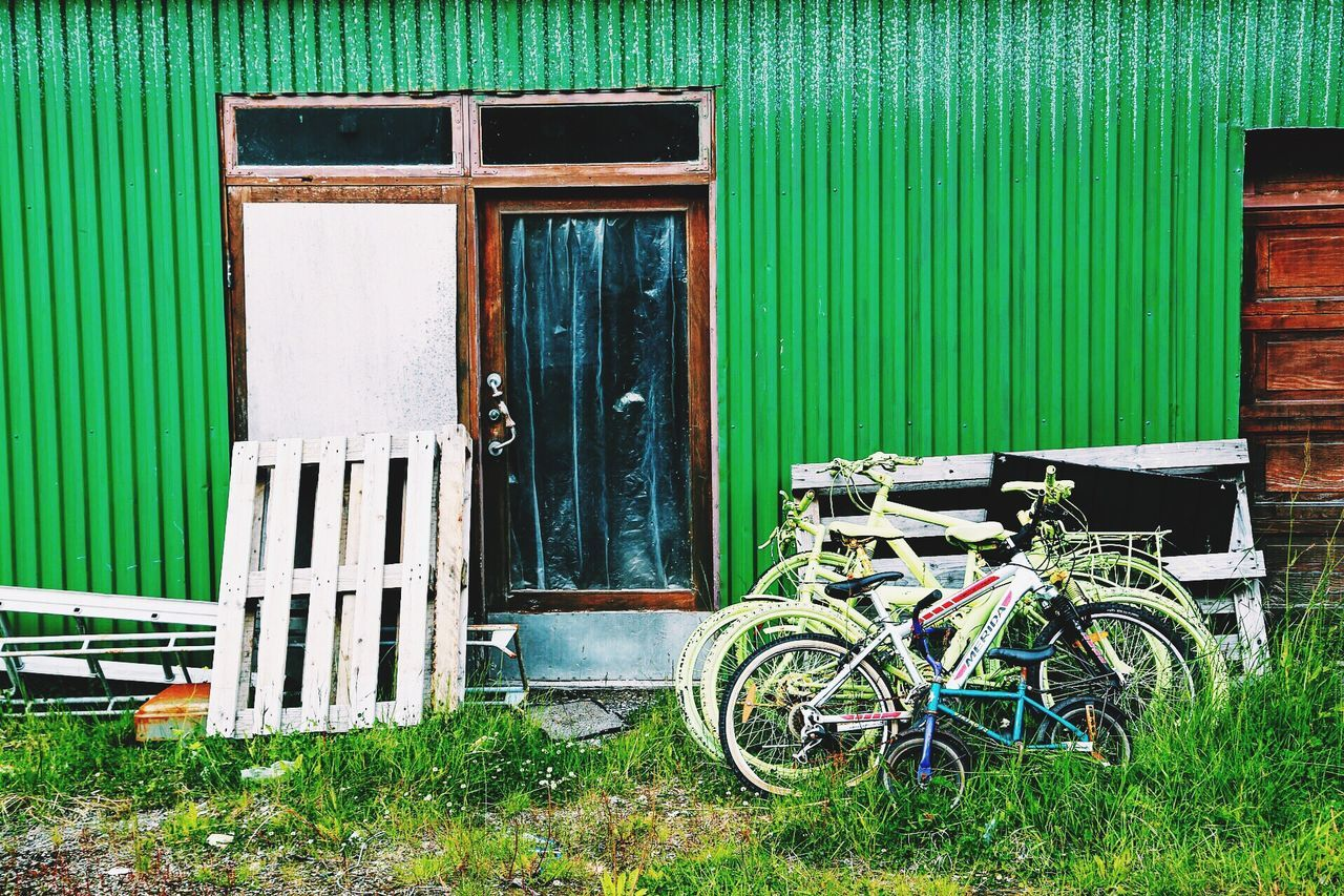 door, green color, day, outdoors, architecture, built structure, no people, building exterior, mode of transport, stationary, transportation, grass, bicycle, close-up