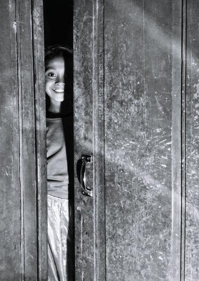 Portrait of smiling girl looking through ajar door