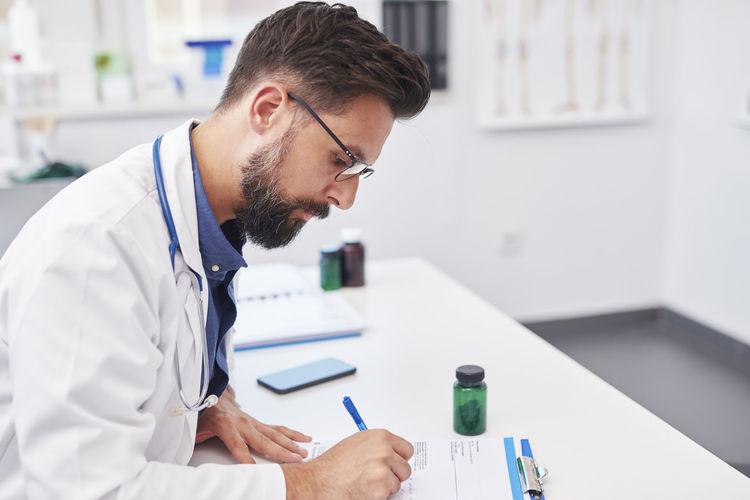 Scientist writing prescription at desk in clinic