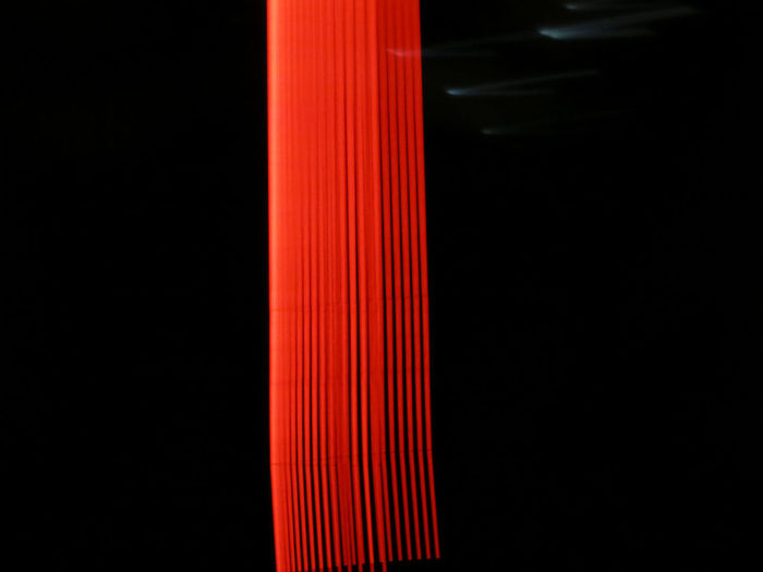 Close-Up Of Red Light Painting Against Black Background