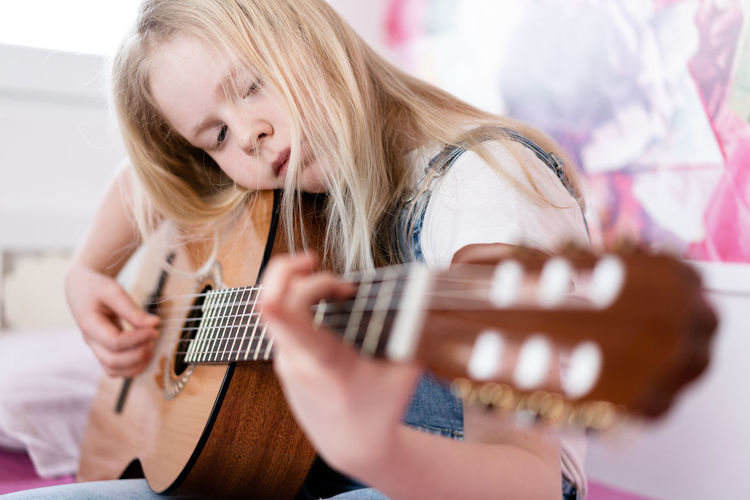 Girl playing guitar while sitting on bed at home