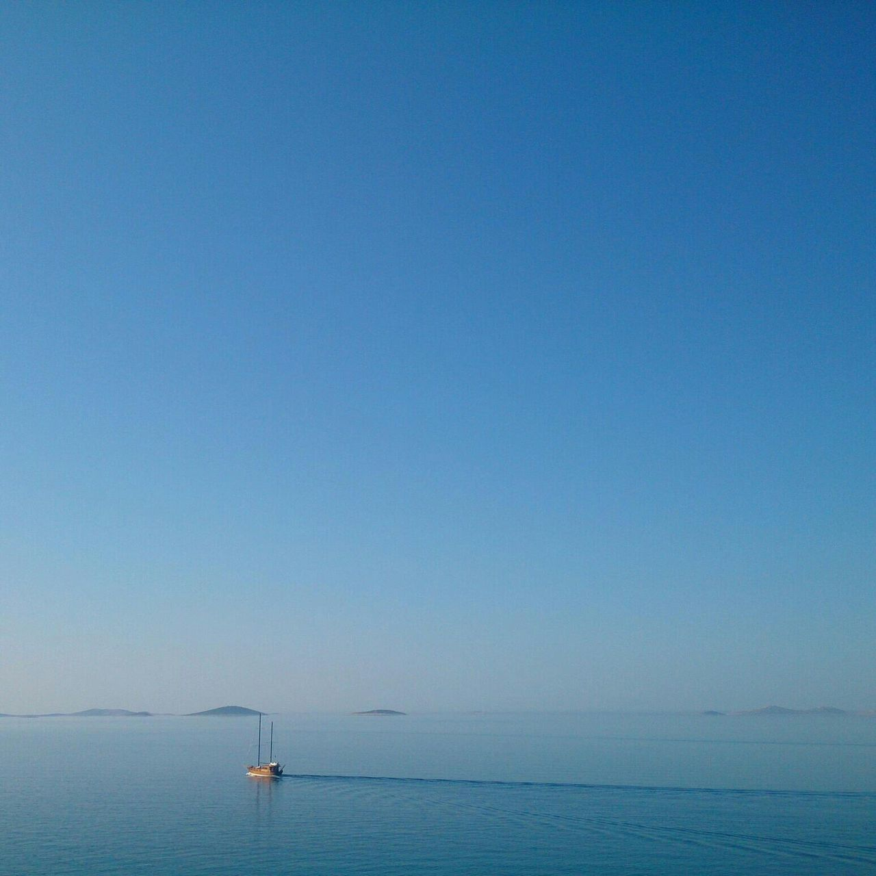 Lone boat at distance in calm blue sea