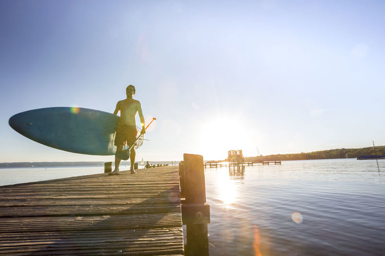 Shirtless man walking with paddleboard on pier over lake against sky