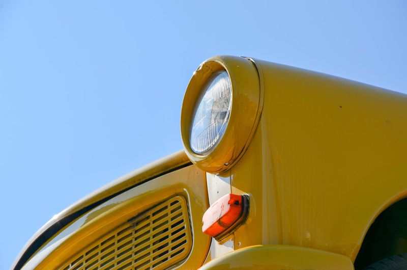 Close-Up Of Yellow Car Against Blue Sky