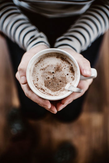 Low section of woman holding hot chocolate at home