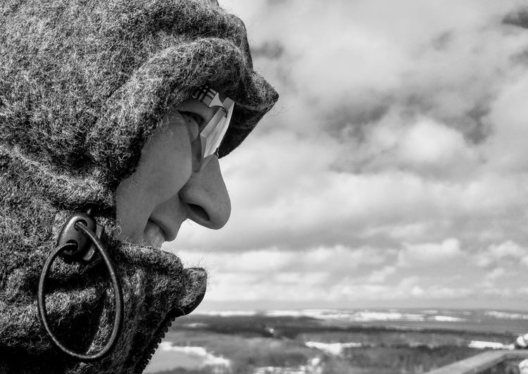 Close-up of man wearing hood against sky