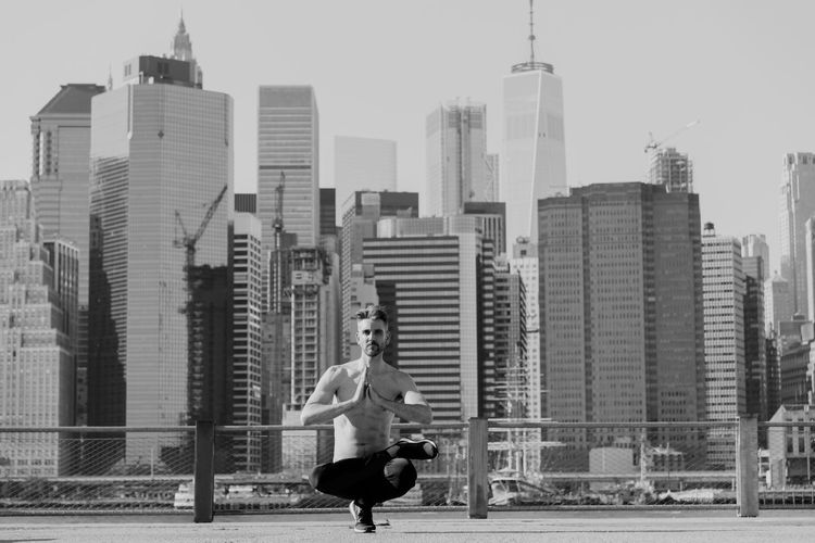 Full length of shirtless mature man practicing yoga on building terrace against one world trade center