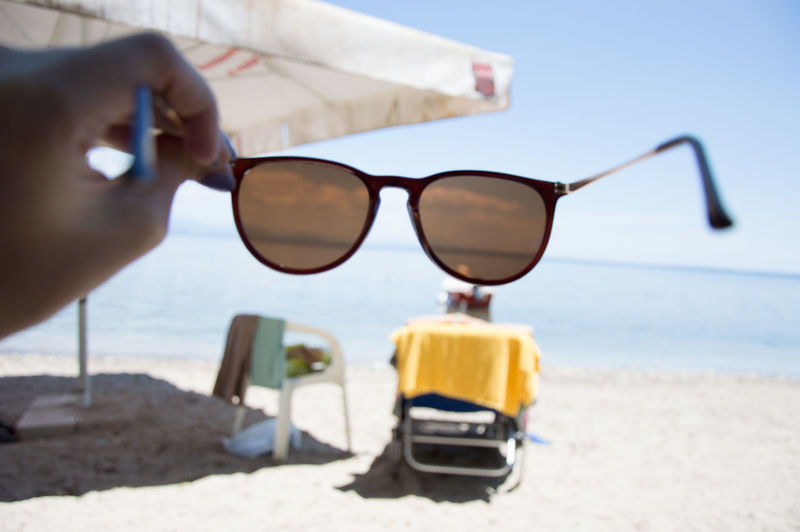 Vacations Beach Close-up Day Eyeglasses  Focus On Foreground Horizon Over Water Human Body Part Human Hand Leisure Activity Lifestyles Nature One Person Outdoors People Real People Sand Sea Sky Sunglasses Sunlight