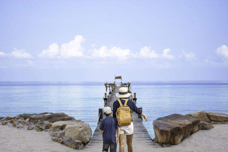 Mother and son walking on wooden bridge pier boat in the sea and the bright sky at Koh Kood, Trat in Thailand. Water Sea Sky Horizon Horizon Over Water Scenics - Nature Beach Beauty In Nature Cloud - Sky Rear View Nature Real People Men Land Tranquil Scene Rock Day Solid People Outdoors