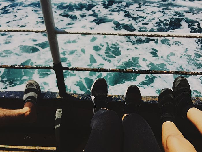 Low section of people by railing over sea