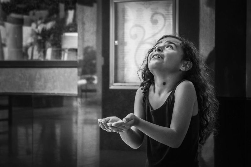Girl gesturing while looking up at home