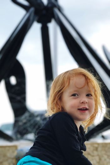 Close-up of girl smiling while sitting against anchor fountain