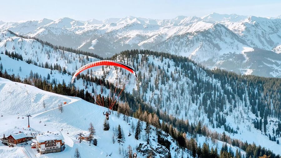 Paraglader over snowy mountains in austria