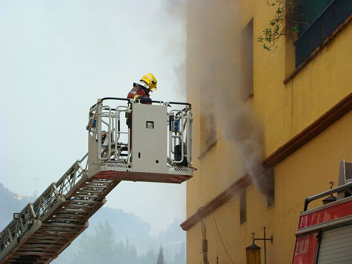 Low Angle View Of Firefighter On Cherry Picker By Smoke Coming Out From Building