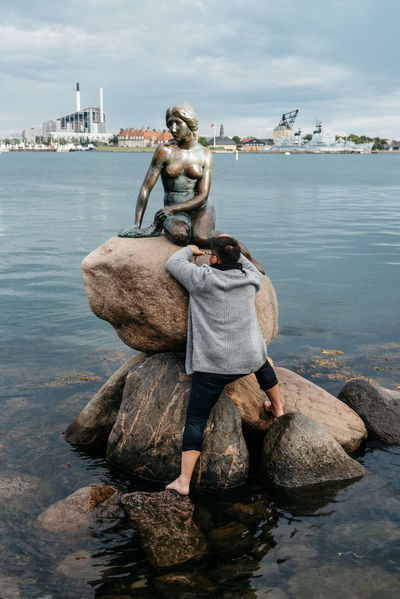 Asian tourist trying to climb on top of Little Mermaid in Copenhagen Climbing Forbidden Full Length Landmark Leisure Activity Little Mermaid  Man Nature Ocean One Person Outdoors Real People Rear View Rock - Object Sea Sea And Sky Sky Tourist Tourist Attraction  Travel Travel Destinations Vandal Vandalism Water Waterfront