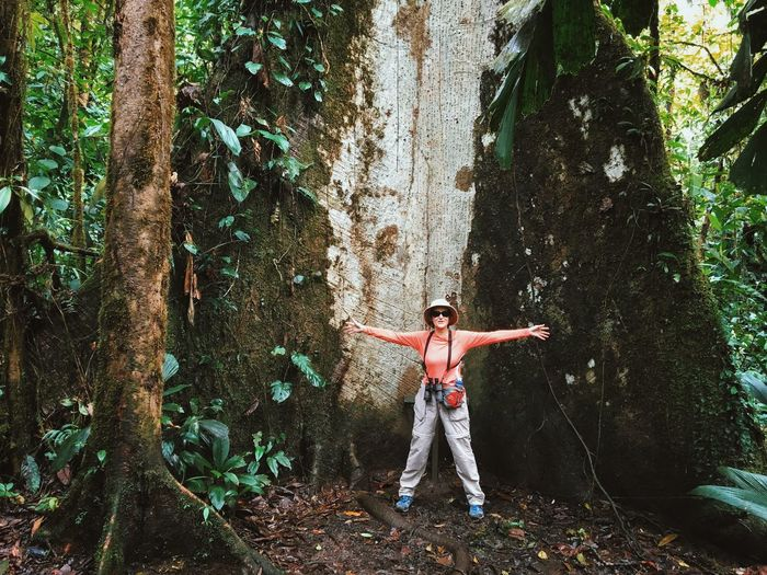 Happy Woman With Arms Outstretched Standing Against Huge Tree At Forest