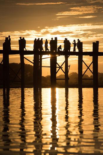 Silhouette people on footbridge over sea against sky during sunset