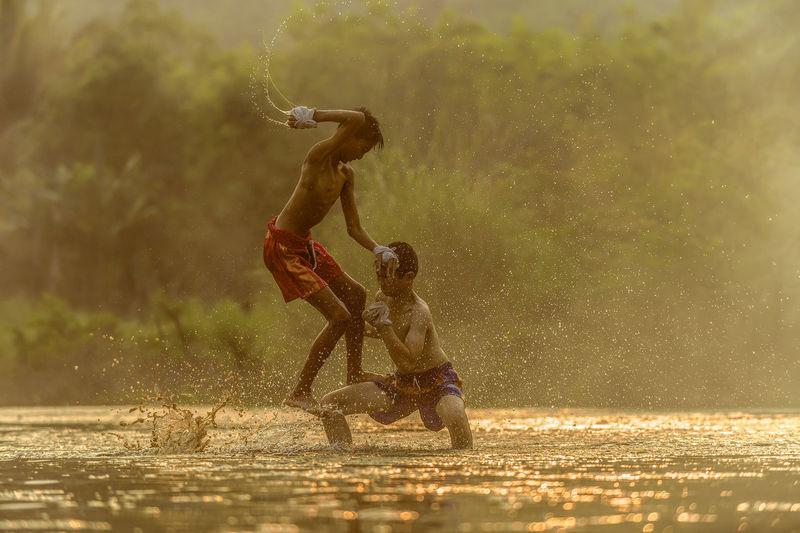Shirtless boys playing in swamp
