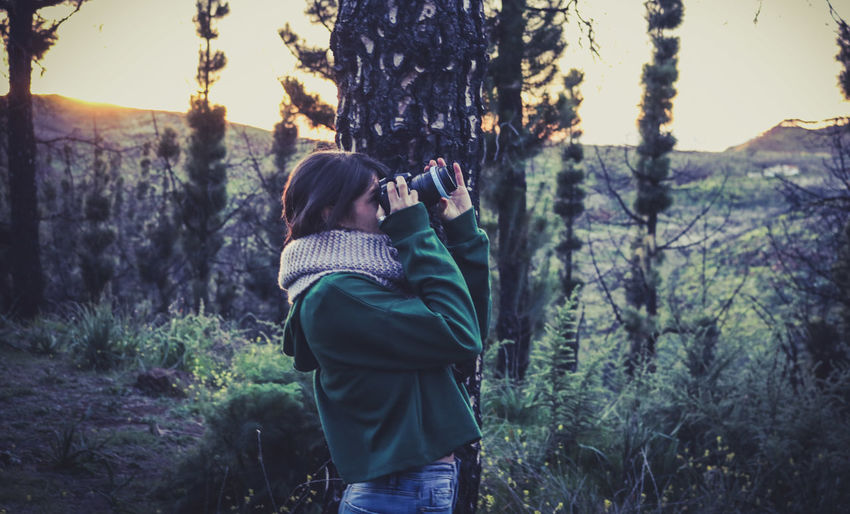 Side view of woman looking through binoculars against trees at forest