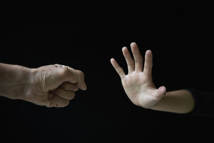 Close-up of people hand against black background