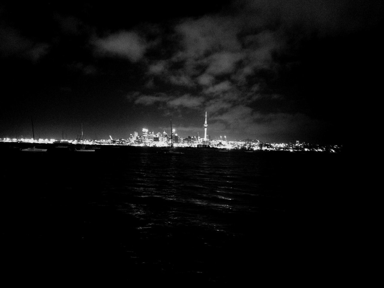 VIEW OF ILLUMINATED CITY BY SEA AGAINST SKY