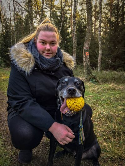 Portrait of young woman with dog in forest