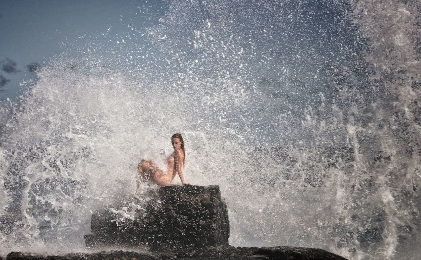 Naked Woman Sitting On Rock By Wave Splashing In Sea