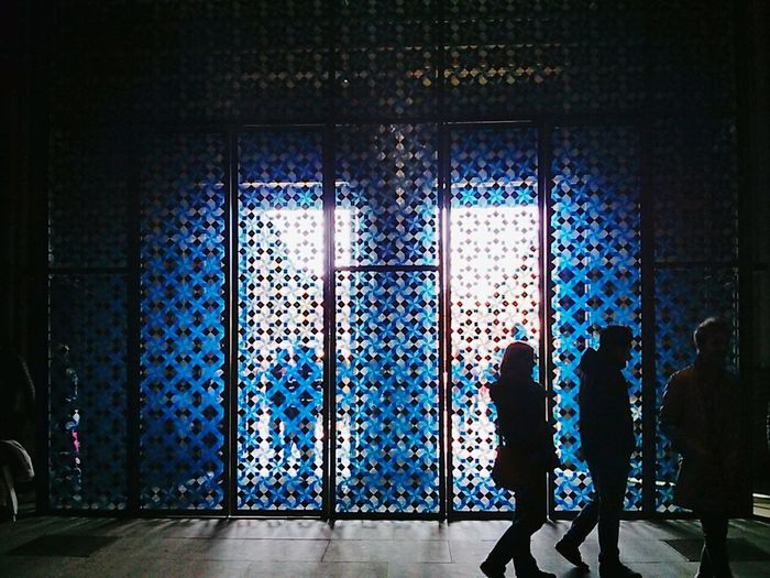 Silhouettes of people against stained glass wall
