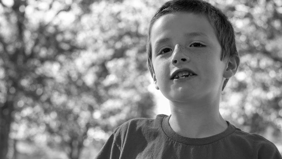 Close-up portrait of boy against trees