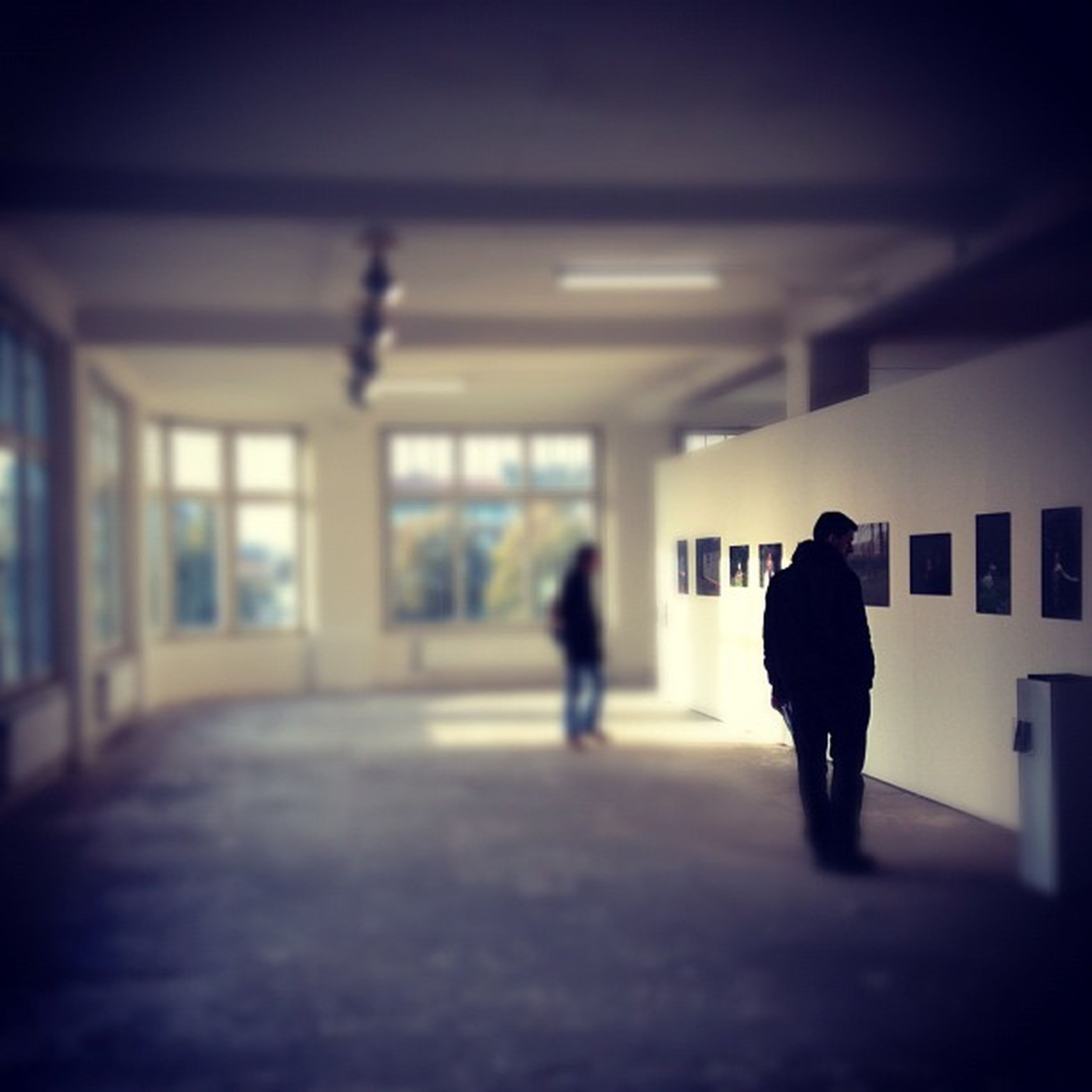 indoors, silhouette, architecture, walking, men, rear view, built structure, full length, lifestyles, window, illuminated, corridor, person, standing, flooring, unrecognizable person, dark