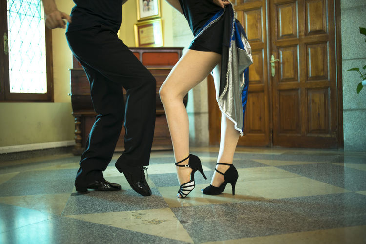 Low section of couple dancing on tiled floor
