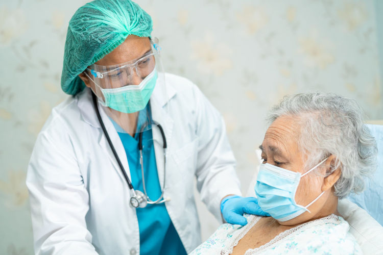Doctor wearing flu mask consoling patient at hospital