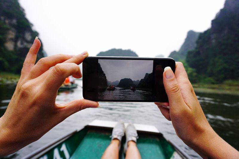 Cropped image of woman photographing sea through smart phone while sitting on boat