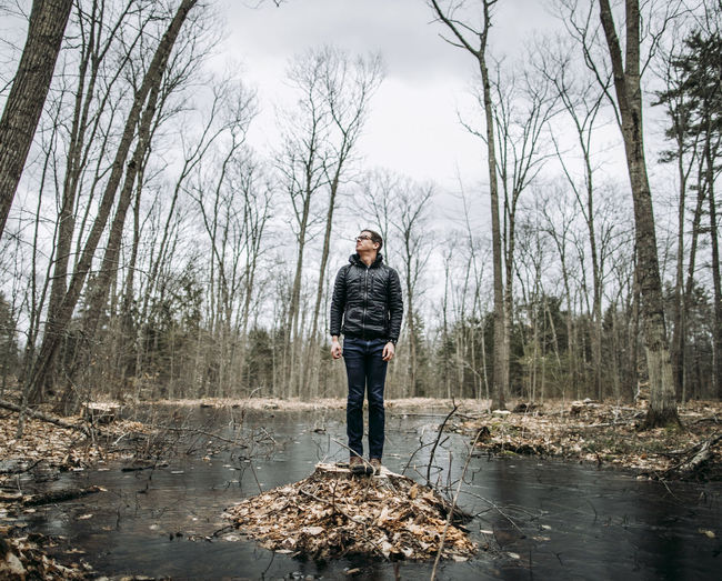 Man standing by bare trees in forest