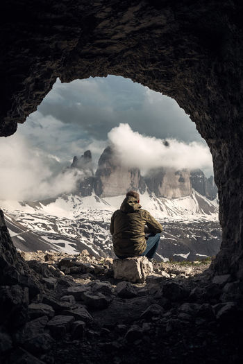 Rear view of man sitting on rock looking at mountains during winter