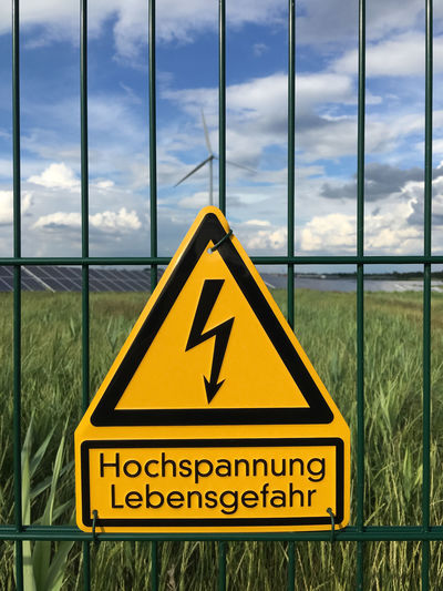 fence with high voltage sign and solar plant Chainlink Fence Cloud Cloud - Sky Danger Fence Focus On Foreground High Voltage High Voltage Sign Information Sign Sign Sign Sky Solar Solar Energy Solar Energy Plant Solar Plant Voltage Warning Warning Sign Warningsign Wind Turbine Yellow