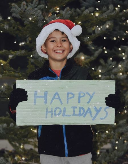 Happy Holidays! Children Elf Happy Holidays Holding Sign Lights Little Boy Little Boys Santa Elves Trees Child Christmas Tree Holiday Collection Merry Christmas Outside At Night Santas Little Helper Seasonal Seasons Greetings Signs And Banners Smiling Snow Snowing Outside We Wish You A Merry Christmas Wearing Santa Hat Wishing You A Happy Holiday Season Young People