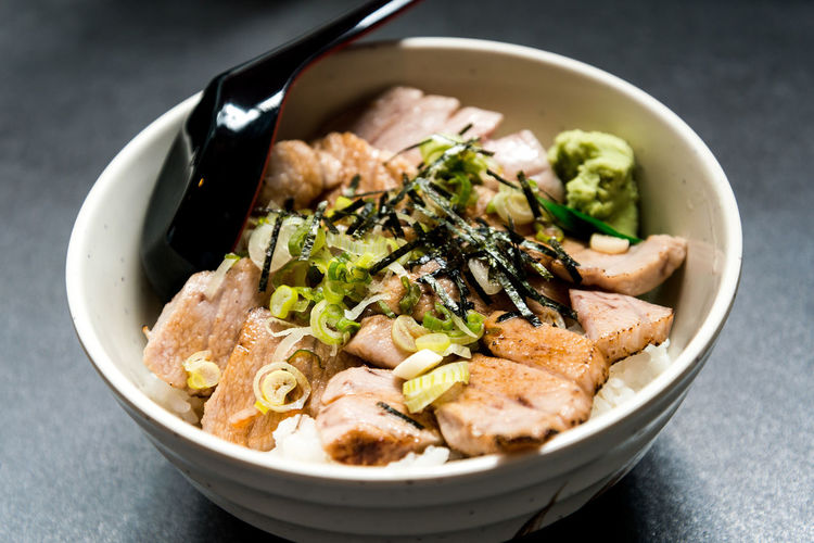 Bowl of rice topped with meat and scallions