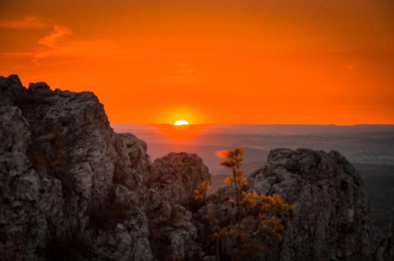 Scenic view of rocks against orange sky