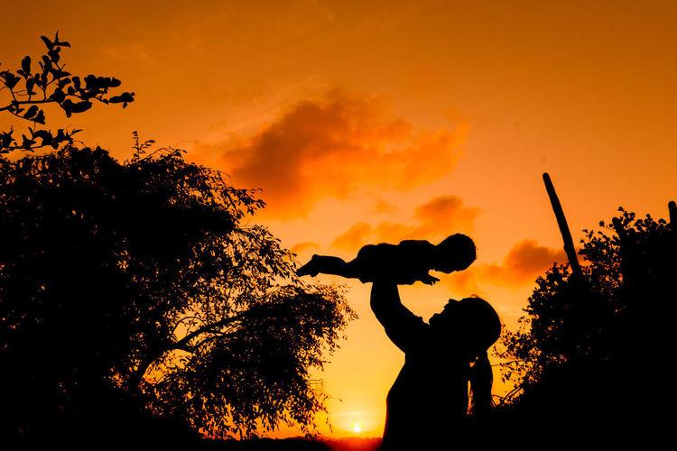 Silhouette people by tree against orange sky