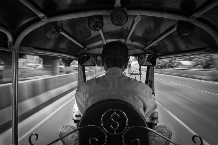 Rear view of man riding jinrikisha in city