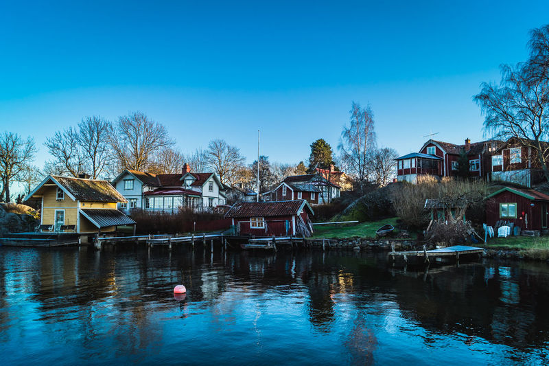 Houses reflection in river at vaxholm against blue sky