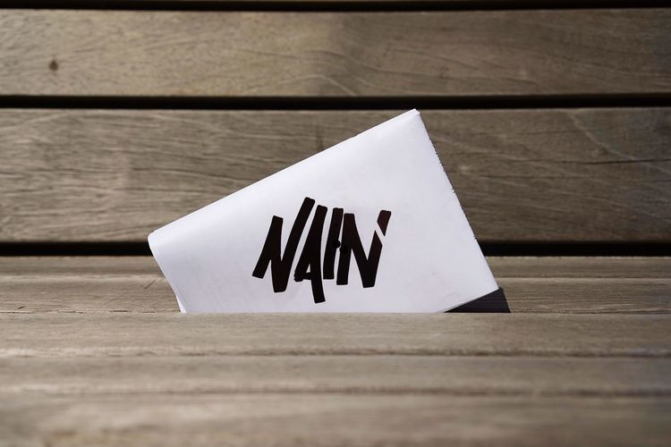 Closeup Bench Nain Graffiti Art Tag Piece Of Paper Wood - Material Paper No People Still Life White Color Day Close-up High Angle View Selective Focus Text Simplicity