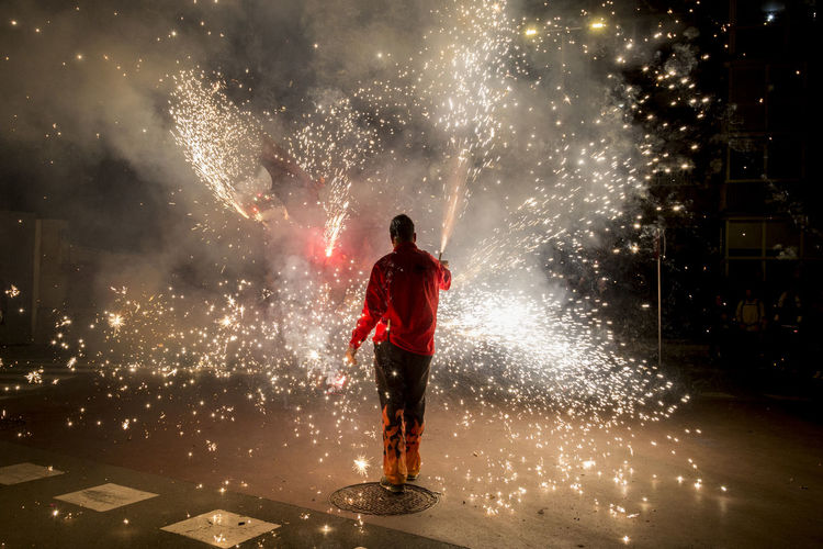 Man with firework display standing on road at night