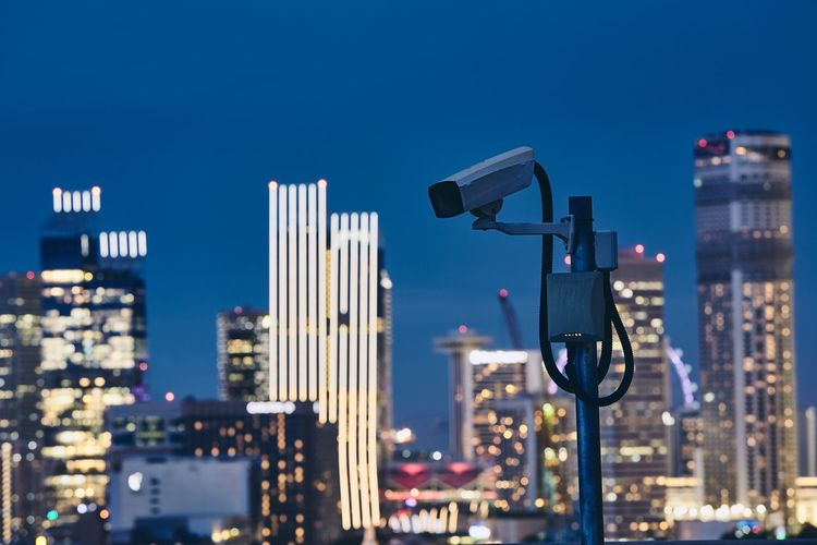 Security camera against illuminated urban skyline at night. Concept of surveillance, protection and safety. Camera City Crime Security Architecture Building Building Exterior Built Structure Cityscape Control Financial District  Illuminated Monitoring Night Nightlife Protection Safety Security Camera Security System Skyscraper Street Light Surveillance Technology Urban Skyline Watching