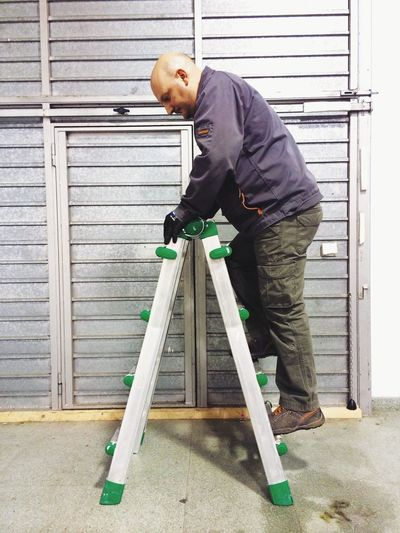 Full length of worker climbing ladder in industry