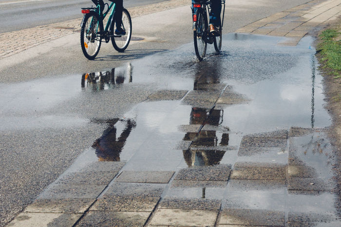 Two man riding bicycle After The Rain Bicycle City Life Lifestyle Men Motion Outdoors People Puddle Reflection Riding Street Streetphotography Transportation Urban Transportation Vintage Bicycles Water Reflections Wet
