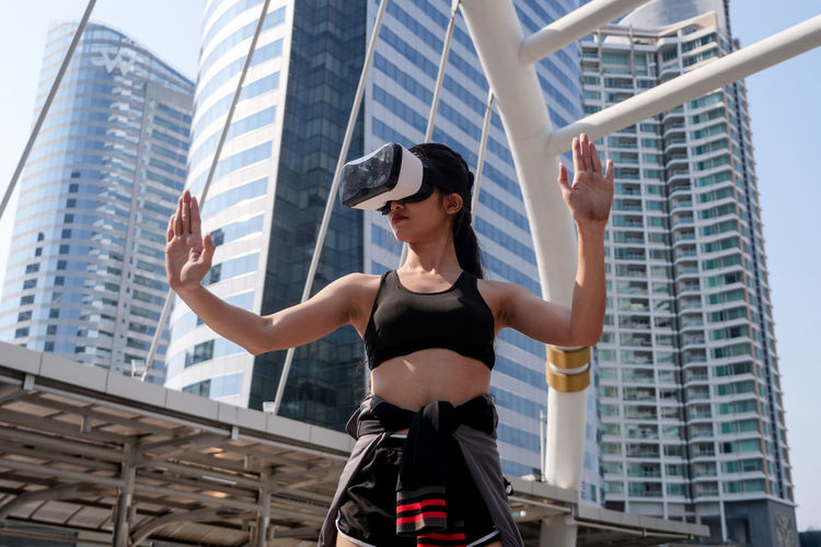 Low angle view of woman using virtual reality simulator in city