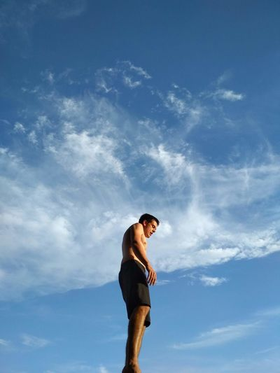 Low angle view of shirtless man standing against sky